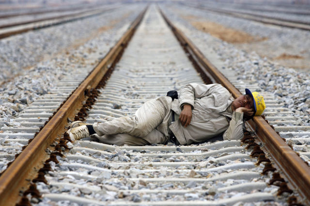 A worker naps on the railway at the construction site of Wuhan North Railway Marshalling Station in Wuhan