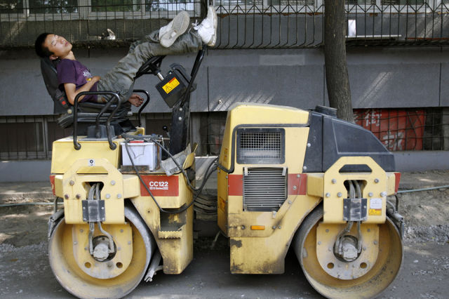 Driver takes nap on a road roller near construction site in Beijing