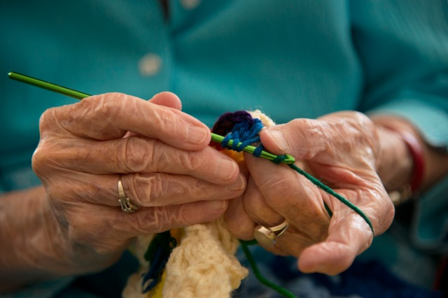 """Working by feel, 101-year-old hands grasp a green crochet needle and guide rainbow-colored yarn through a cluster then out of it to catch the yarn and pull it through again. She misses. She tries again, and misses once more, sometimes three times before successfully completing one stitch. Jerry Dillon can only see a grey hole where her beloved project is, having lost most of her sight to macular degeneration in 1998. """"I guess I'm pretty stubborn,"""" she said. """"I'm not going to give up."""" Dillon has been sewing, knitting and crocheting for charity since the 1940s and doesn't intend to stop. She's discovered one last crochet stitch that she can accomplish despite her blindness, and she gives the afghans that she works on each day to Project Linus, a group that provides handmade blankets to children in need. She never meets the people who receive her fruits of her labor but she knows that they are appreciated. """"I hope that it'll keep them warm and they will give something to someone else afterwards,"""" she said. """"That's how payback works."""" Photographed July 2, 2012."""